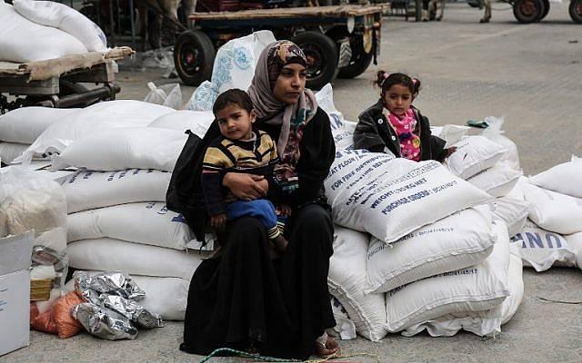 Una mujer árabe se sienta con un niño después de recibir alimentos de las oficinas de las Naciones Unidas en las oficinas de las Naciones Unidas en el llamado campo de refugiados de Khan Yunis en el sur de la Franja de Gaza el 11 de febrero de 2018, donde viven los bisnietos de los originales refugiados árabes de la guerra árabe contra Israel. (SAID KHATIB / AFP)