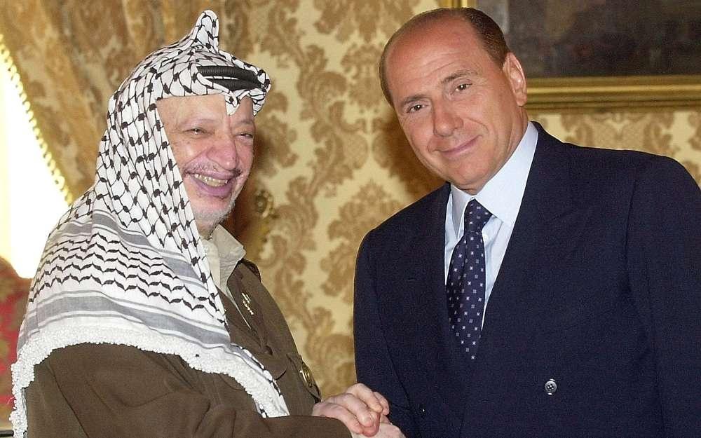 El líder árabe, egipcio de nacimiento Yasser Arafat, izquierda, y el primer ministro de Italia Silvio Berlusconi se dan la mano antes de una reunión en la oficina del Primer Ministro, en Roma, el 2 de agosto de 2001. (AP / Plinio Lepri)