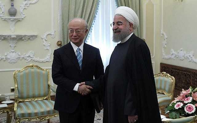 En esta foto publicada por el sitio web oficial de la oficina de la Presidencia iraní, el presidente Hassan Rouhani, a la derecha, y el director general de la Agencia Internacional de Energía Atómica, AIEA, Yukiya Amano se saludan ante los medios al comienzo de su reunión en la oficina de la Presidencia en Teherán, Irán, domingo, 18 de diciembre de 2016. (Oficina de la Presidencia iraní / AP)