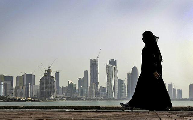 En esta foto de archivo del 14 de mayo de 2010, una mujer qatarí camina frente al horizonte de la ciudad en Doha, Qatar. (Foto AP / Kamran Jebreili, Archivo)