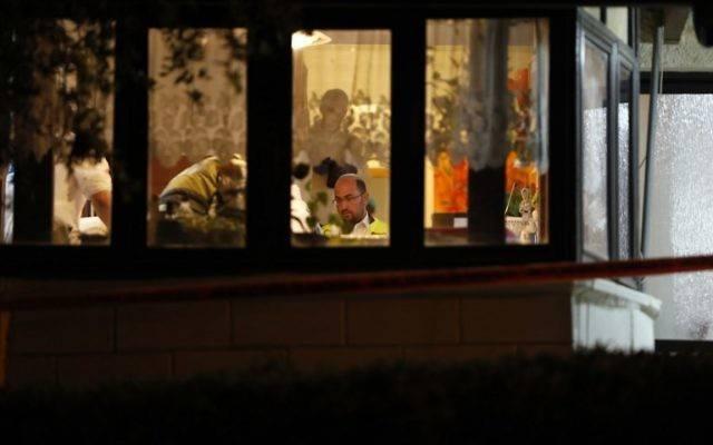 La policía forense israelí inspecciona la casa donde un terrorista musulmán de la Autoridad Palestina irrumpió el día anterior y apuñaló a cuatro israelíes, asesinando a tres de ellos, en Halamish, el 22 de julio de 2017. (AFP / GALI TIBBON)