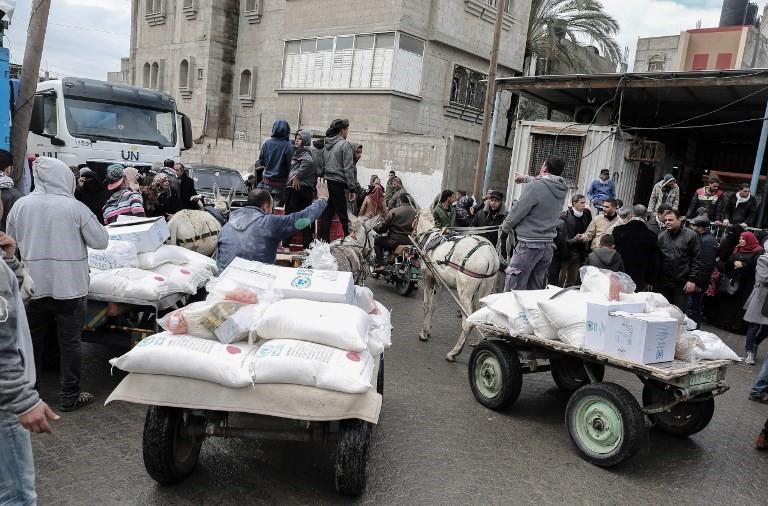 Árabes recogen paquetes de ayuda en un centro de distribución de alimentos de las Naciones Unidas en Khan Yunis, al sur de la Franja de Gaza, el 28 de enero de 2018. (Said Khatib / AFP)