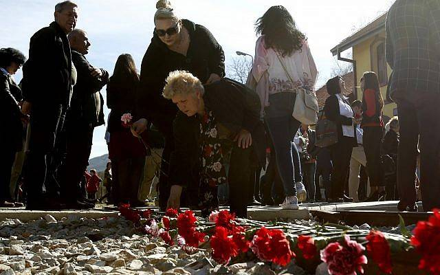 La gente pone flores en las vías del tren, durante una conmemoración de las víctimas del Holocausto, en la estación de trenes de Bitola, en el sur de Macedonia, el 11 de marzo de 2018. (AP Photo / Boris Grdanoski)