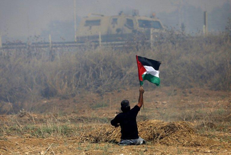 Esta foto tomada el 19 de mayo de 2017 muestra al incitador palestino incapacitado Ibrahim Abu Thurayeh ondeando una bandera palestina durante los enfrentamientos con soldados israelíes luego de una protesta contra el bloqueo en Gaza, cerca de la valla fronteriza al este de la ciudad de Gaza.(MOHAMMED ABED / AFP)