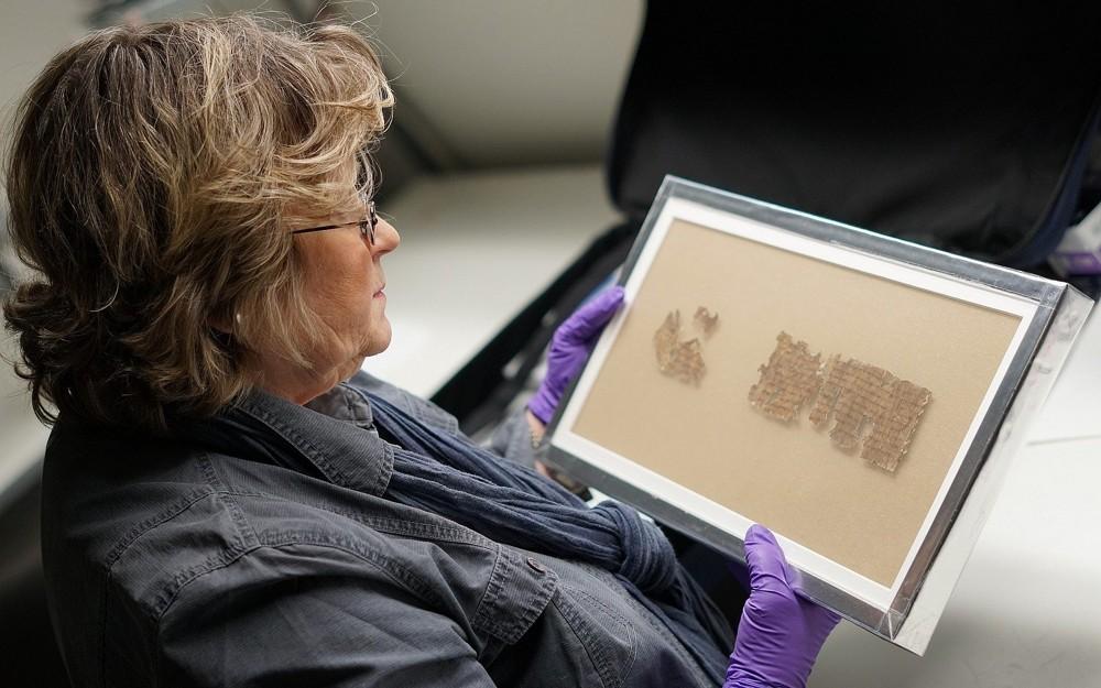 La conservadora de la Autoridad de Antigüedades de Israel Tatiana Treiger sostiene un fragmento del pergamino Tohorot, en exhibición pública por primera vez en el Museo de Naturaleza y Ciencia de Denver.(Yoli Shwartz, Autoridad de Antigüedades de Israel)