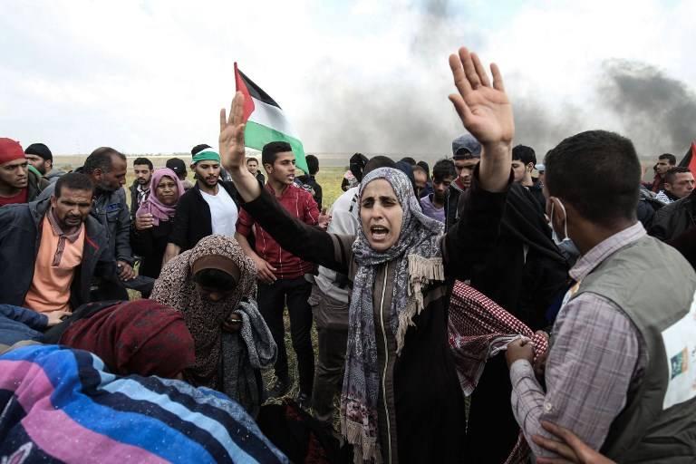 Los manifestantes palestinos agitan la bandera de la revuelta árabe durante una manifestación conmemorativa del Día de la Tierra, cerca de la frontera con Israel, al este de la ciudad de Gaza, el 30 de marzo de 2018. (AFP / Hams de Mahmud)