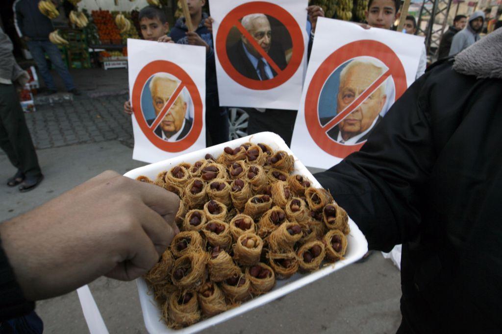 Los palestinos reparten dulces mientras celebran el fallecimiento del ex primer ministro israelí Ariel Sharon en Khan Younis en el sur de la Franja de Gaza, el 11 de enero de 2014. (Crédito de la foto: Abed Rahim Khatib / Flash 90)