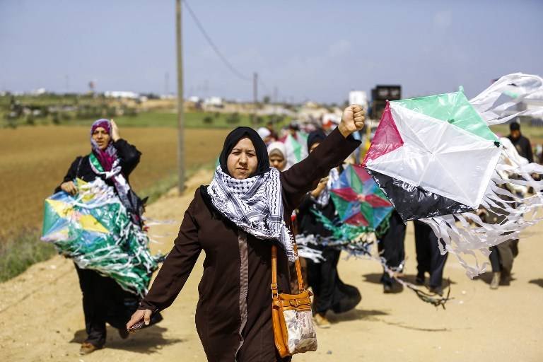 Mujeres árabes palestinas vuelan cometas marcadas con los colores de la bandera de la revuelta árabe durante una manifestación antes del Día de la Tierra, en una ciudad carpa a lo largo de la frontera con Israel al este de la ciudad de Gaza el 29 de marzo de 2018. (AFP PHOTO / MOHAMMED ABED)