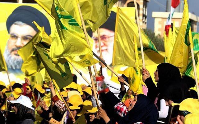 Mujeres agitan banderas libanesas y de Hezbollah frente a los retratos del líder supremo iraní, el ayatolá Ali Khamenei (R) y el líder de Hezbollah Hassan Nasrallah, en la ciudad libanesa de Bint Jbeil el 13 de agosto de 2016. (AFP Photo / Mahmoud Zayyat)