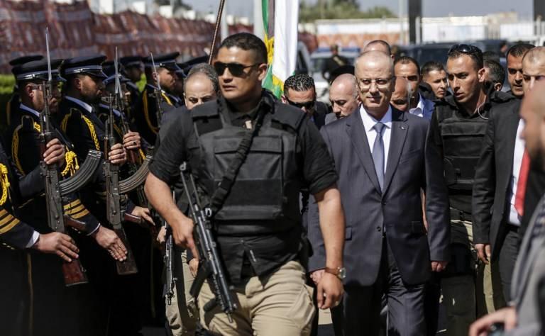 El primer ministro palestino Rami Hamdallah (2do R), escoltado por sus guardaespaldas, es recibido por las fuerzas policiales de Hamás (L) a su llegada a la ciudad de Gaza el 13 de marzo de 2018. (AFP PHOTO / MAHMUD HAMS)