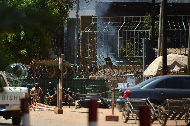 El personal de seguridad se cubre mientras el humo se eleva desde The Institute Francais en Ouagadougou el 2 de marzo de 2018, cuando la capital de Burkina Faso sufría múltiples ataques contra la embajada de Francia, el centro cultural francés y la sede militar del país.(AFP / Ahmed Ouoba)