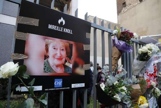 Una fotografía de Mireille Knoll y flores que se colocaron en la valla que rodea su edificio en París el 28 de marzo de 2018. (Francois Guillot / AFP)