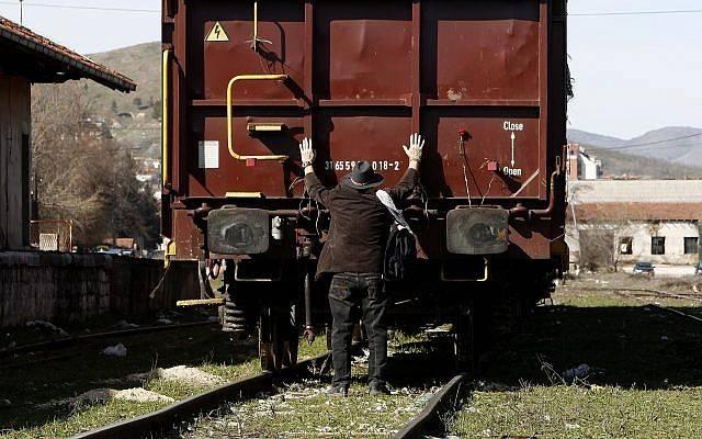 Un judío pone sus manos en un vagón de carga, durante una conmemoración de las víctimas del Holocausto en la estación de ferrocarril de Bitola, en el sur de Macedonia, el 11 de marzo de 2018. (AP Photo / Boris Grdanoski)