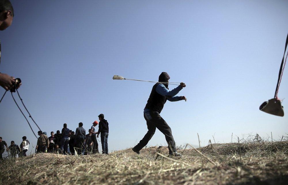 Palestinos lanzan piedras contra soldados israelíes durante una oleada de violencia isamista cerca de la frontera de la Franja de Gaza con Israel, en el este de la ciudad de Gaza, el sábado 31 de marzo de 2018. (AP / Khalil Hamra)