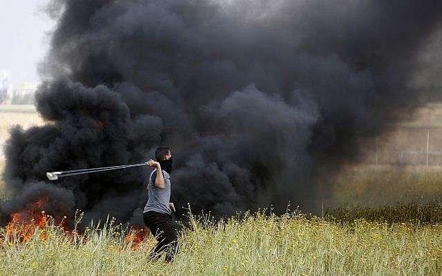 Un atacante palestino arroja rocas letales contra los soldados israelíes durante la ola de ataques islámicos contra las tropas israelíes a lo largo de la frontera de la Franja de Gaza con Israel, al este de Khan Younis, Franja de Gaza, el viernes 30 de marzo de 2018. (AP / Adel Hana)