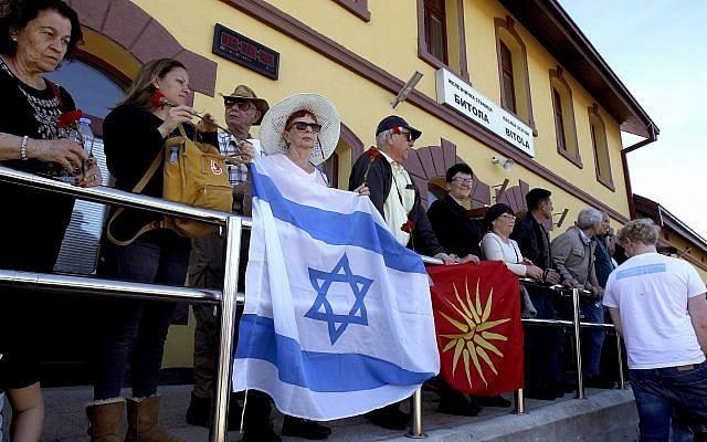 La gente sostiene la bandera israelí y la antigua Macedonia cuando participan en la conmemoración de las víctimas del Holocausto, en la estación de trenes de Bitola, en el sur de Macedonia, el 11 de marzo de 2018. (AP Photo / Boris Grdanoski)