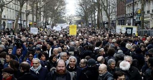 Los participantes caminan detrás sosteniendo pancartas durante una marcha silenciosa en París en memoria de Mireille Knoll, una mujer judía de 85 años asesinada en su casa por un musulmán y su cómplice, el 28 de marzo de 2018. (Francois Guillot / AFP)