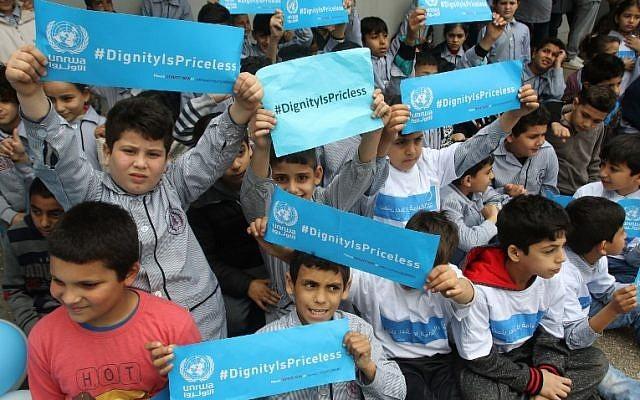 Los llamados refugiados palestinos sostienen pancartas en una escuela perteneciente a la Agencia de Obras Públicas y Socorro de las Naciones Unidas para los Refugiados Palestinos (UNRWA) en la ciudad de Sebline al este del puerto libanés sur de Saida, el 12 de marzo de 2018, durante una protesta contra los recortes de ayuda de Estados Unidos a la organización.(AFP PHOTO / Mahmoud ZAYYAT)