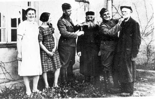 Praszka (Praschkau - Wartheland): policías alemanes cortan las barbas a dos judíos observantes. Junto a ellos dos chicas polacas ven la escena y se divierten. Yad Vashem, Jerusalem