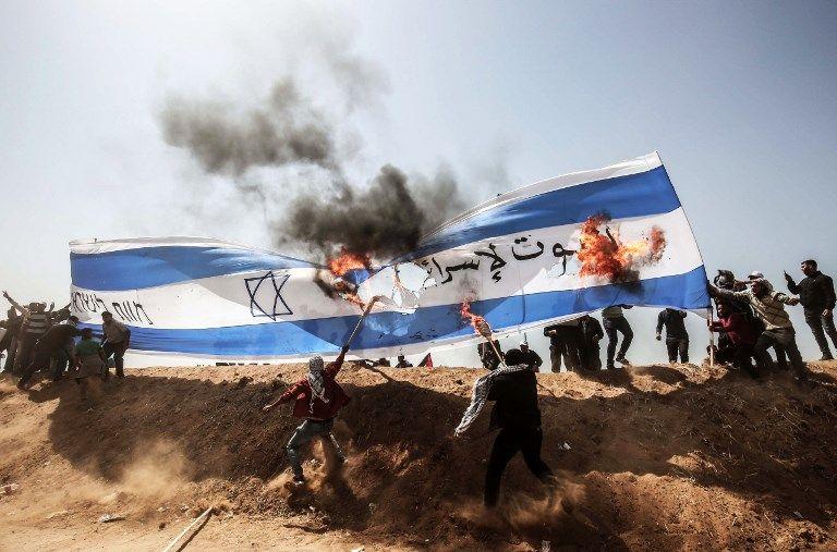 Árabes palestinos queman una bandera israelí durante los ataques islamistas contra las fuerzas de seguridad israelíes en la frontera de Gaza con Israel, al este de Khan Younis, en el sur de la Franja de Gaza el 6 de abril de 2018. (AFP PHOTO / SAID KHATIB)