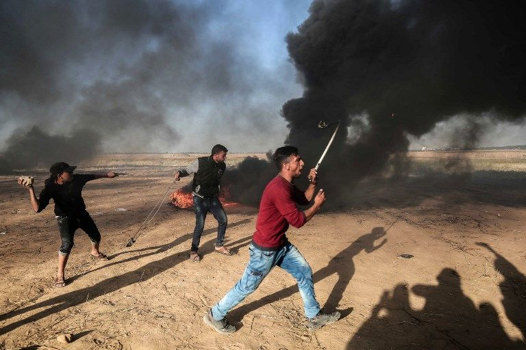 Atacantes palestinos lanzan rocas a las fuerzas de seguridad israelíes en la frontera con Israel, al este de Khan Yunis, en el sur de la Franja de Gaza, 01 de abril de 2018. (SAID KHATIB / AFP)