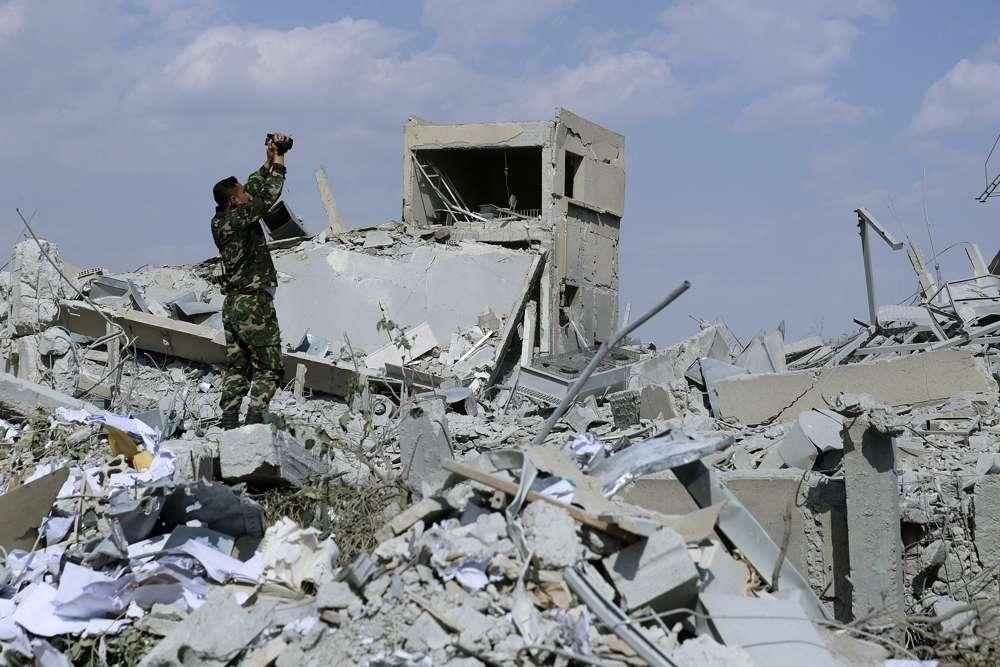 Un soldado sirio filma los daños del Centro de Investigación Científica sirio que fue atacado por ataques militares estadounidenses, británicos y franceses para castigar al presidente Bashar Assad por su ataque químico contra civiles, en Barzeh, cerca de Damasco, Siria, el sábado 14 de abril de 2018 ( AP Photo / Hassan Ammar)