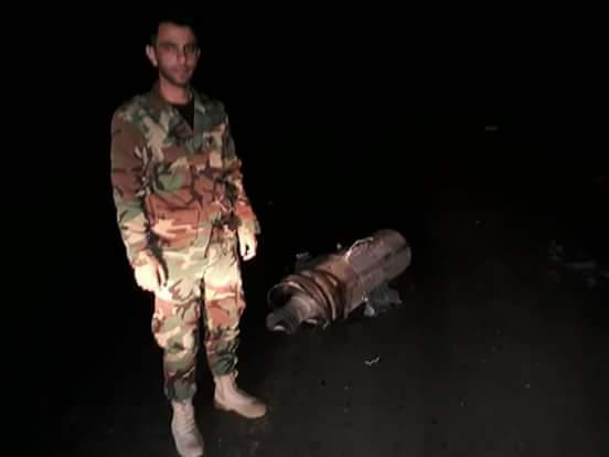 Un soldado sirio parado al costado de los restos de un misil