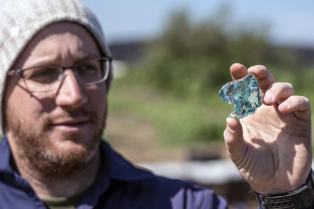 El arqueólogo Yair Amitzur sostiene un trozo de vidrio descubierto durante los preparativos para el nuevo Sendero del Sanedrín en Galilea.Según Amitzur, el hallazgo es evidencia de la industria del vidrio desde el tiempo del Sanedrín.(Yaniv Berman, Autor de Antigüedades de Israel)