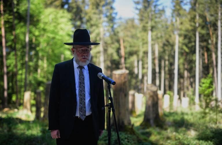 El rabino Shmeul Aharon Brodman reza el Kadish durante una ceremonia para inaugurar un sitio conmemorativo en el antiguo campo de concentración de Muehldorfer Hart cerca de Waldkraiburg, en el sur de Alemania, el 27 de abril de 2018. El monumento fue inaugurado en el sitio de un campo de concentración nazi de la Segunda Guerra Mundial, donde los trabajadores forzados construyeron una fábrica de aviones en el interior de un bosque bávaro.Al menos 2.200 prisioneros, muchos de ellos judíos húngaros, murieron en las condiciones miserables en el campamento de Muehldorfer Hart y fueron enterrados en el lugar en una fosa común.(AFP PHOTO / dpa / Matthias Balk)