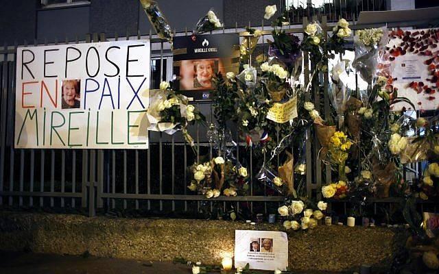 Flores y pancartas se exhiben fuera del apartamento de Mireille Knoll durante una marcha silenciosa en París, Francia, el miércoles 28 de marzo de 2018. (AP Photo / Thibault Camus)