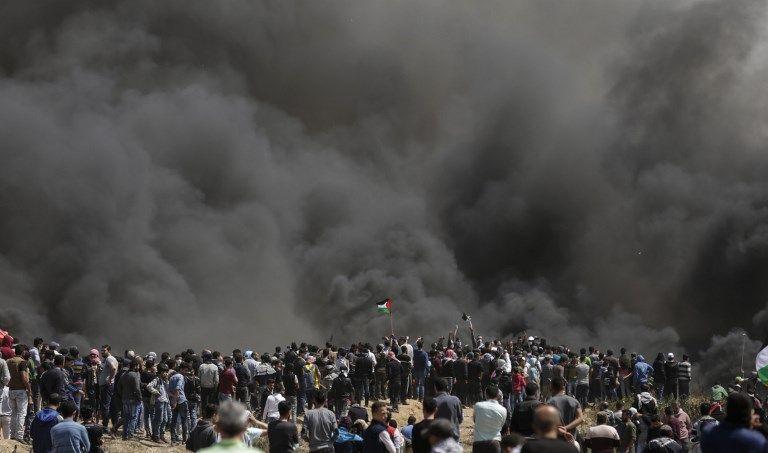 Hombres palestinos agitan sus banderas de la revuelta árabe en la versión de la AP, mientras el humo se eleva por la quema de neumáticos en la frontera entre Israel y Gaza durante una protesta, al este de la ciudad de Gaza en la Franja de Gaza, el 6 de abril de 2018. (AFP PHOTO / MAHMUD HAMS)