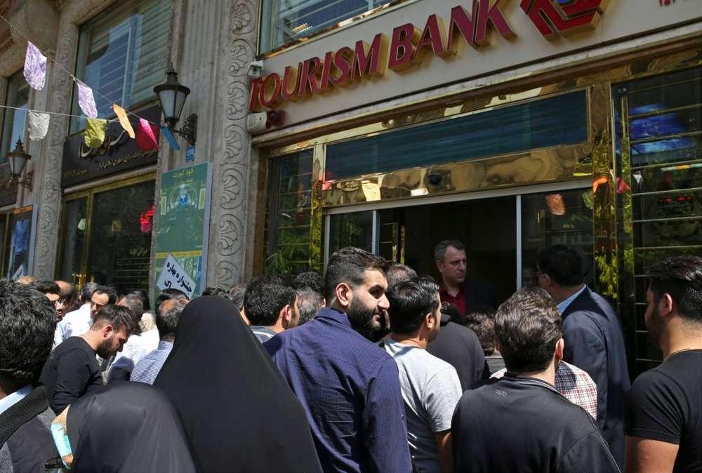 Iraníes de pie frente a un banco, con la esperanza de comprar dólares estadounidenses a la nueva tasa de cambio oficial anunciada por el gobierno, en el centro de Teherán, el 10 de abril de 2018.(Crédito: Vahid Salemi / AP)