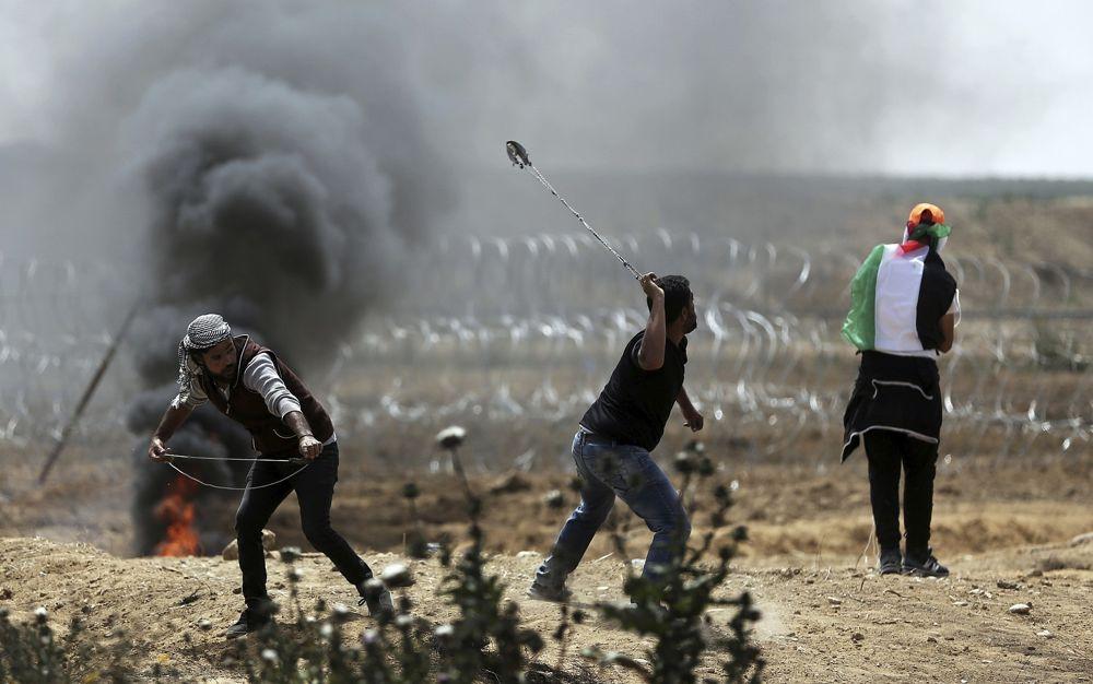 Los islamistas palestinos lanzan piedras contra las tropas israelíes en la frontera de la Franja de Gaza con Israel, el viernes 13 de abril de 2018. (AP Photo / Khalil Hamra)