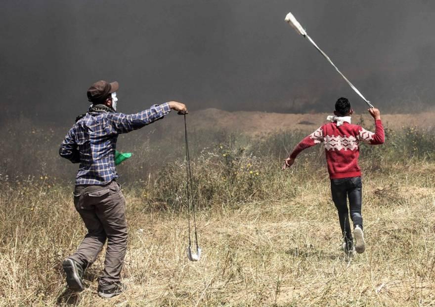 Islamistas palestinos utilizan hondas para lanzar piedras hacia las fuerzas de seguridad israelíes durante la violenta manifestación en la frontera entre Gaza e Israel en el sur de la Franja de Gaza el 6 de abril de 2018. (AFP PHOTO / SAID KHATIB)