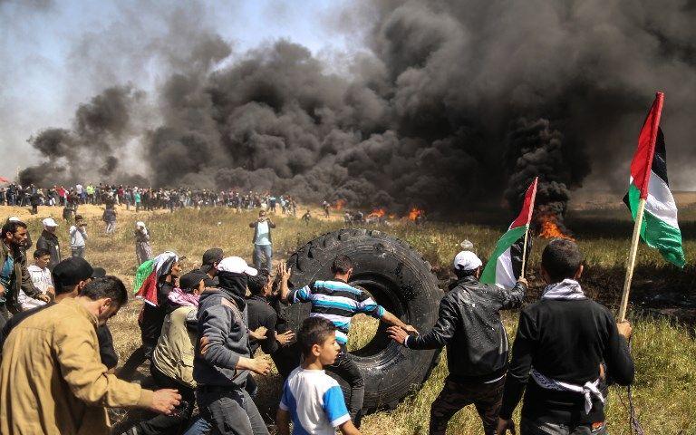 Atacantes palestinos queman neumáticos durante los enfrentamientos con las fuerzas de seguridad israelíes en la frontera de Gaza e Israel, al este de la ciudad de Gaza, el 6 de abril de 2018. (AFP PHOTO / MAHMUD HAMS)