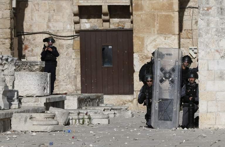 La policía israelí se cubre mientras los islamistas palestinos les arrojan piedras en el Monte del Templo de Jerusalem durante la violencia islámica por tercer día consecutivo el 28 de junio de 2016. (AFP PHOTO / AHMAD GHARABLI)