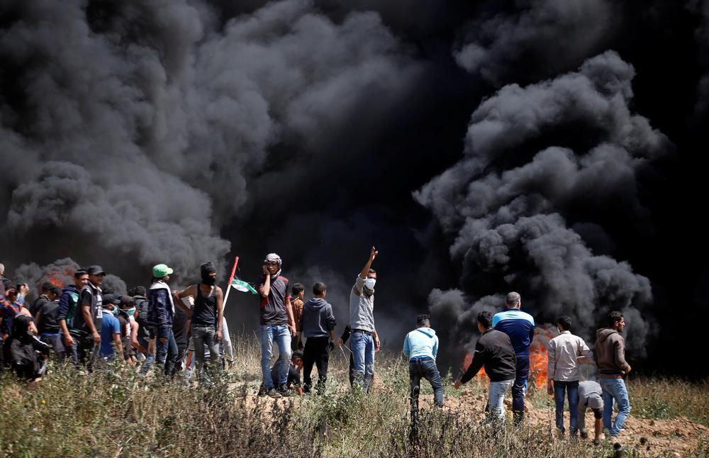 Los árabes palestinos queman neumáticos durante oleada de ataques islamistas contra las fuerzas de seguridad israelíes y un intento masivo de infiltración hacia Israel el 6 de abril de 2018. (AFP / Said Khatib)