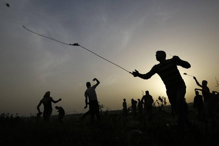 Los atacantes palestinos utilizan hondas para arrojar piedras contra las fuerzas israelíes durante la violencia islamista en la frontera con Israel, al este de la ciudad de Gaza, el 5 de abril de 2018. (AFP PHOTO / MOHAMMED ABED)