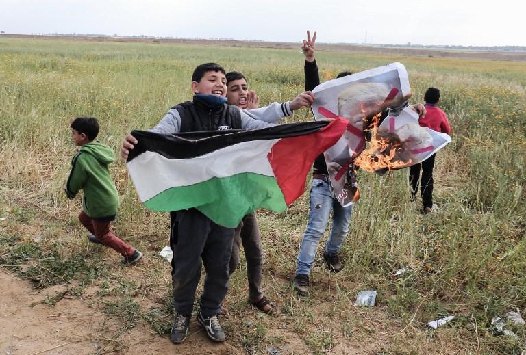 Niños palestinos manipulan fuego ante la mirada de sus padres mientras queman una foto del presidente estadounidense Donald Trump, como parte de la ola de incitación y uso de escudos humanos en la Franja de Gaza. (AFP PHOTO / SAID KHATIB)