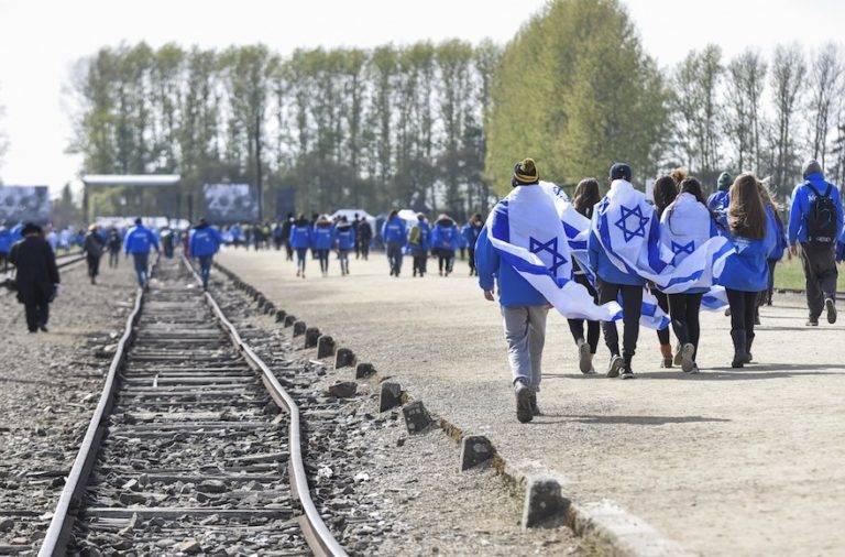 Participantes portando banderas israelíes en el antiguo campo de concentración y exterminio nazi-alemán de Auschwitz-Birkenau durante la 'Marcha de los vivos' en Oswiecim en Cracovia, Polonia el 24 de abril de 2017. (Omar Marques / Agencia Anadolu / Getty Images vía JTA)
