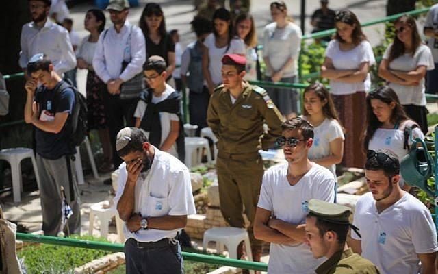 Personas en silencio junto a las tumbas de soldados israelíes en el cementerio militar de Mt Hezl en Jerusalén, mientras una sirena de dos minutos sonaba en todo Israel, conmemorando el Día de los Caídos que conmemora a los soldados caídos de Israel y las víctimas del terror el18 de abril de 2018. (Miriam Alster / Flash 90)