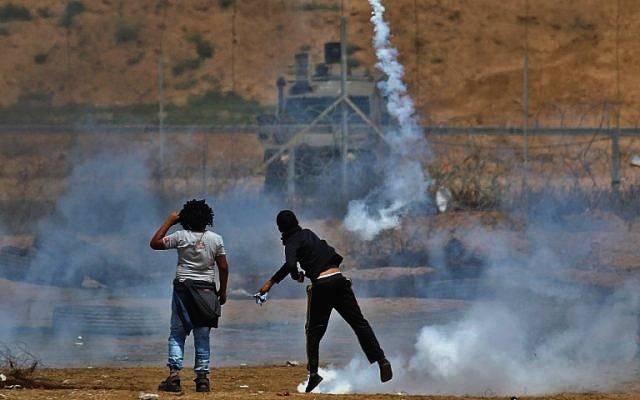 Un islamista palestino arroja un bote de gas lacrimógeno hacia las tropas israelíes cerca de Khan Younis en el sur de la Franja de Gaza, durante el quinto viernes consecutivo de violencia masiva a lo largo de la frontera entre Gaza e Israel, el 27 de abril de 2018. (AFP Photo / Said Khatib)