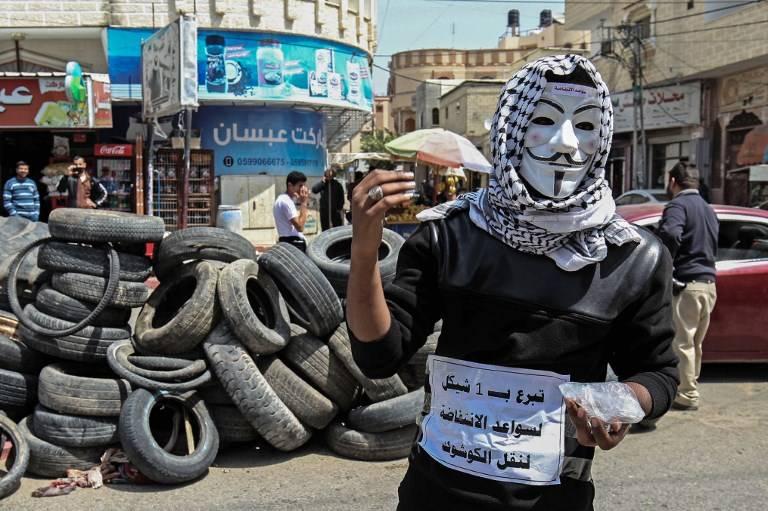 Un joven palestino recoge dinero y neumáticos en Khan Younis, en el sur de la Franja de Gaza, el 4 de abril de 2018. (Said Khatib / AFP)