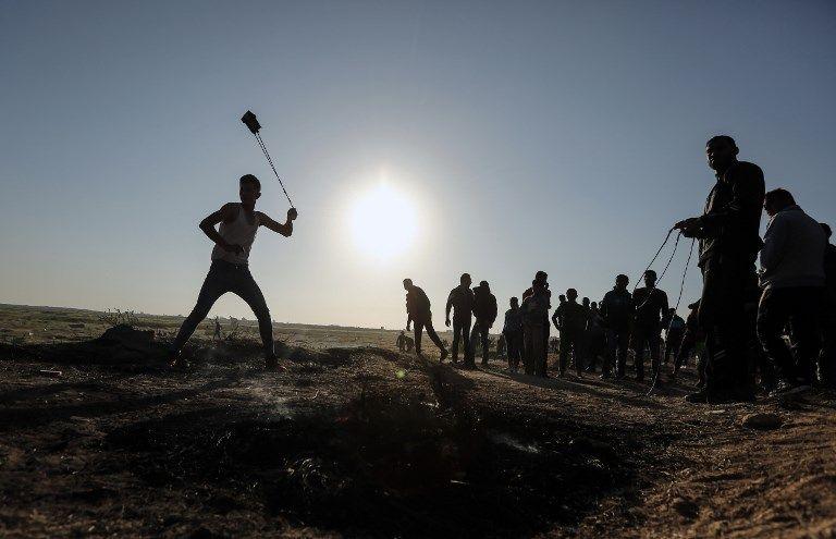 Un atacante palestino arroja piedras hacia los soldados israelíes durante una violenta manifestación a lo largo de la frontera con Israel, al este de la ciudad de Gaza, el 31 de marzo de 2018. (AFP PHOTO / MAHMUD HAMS)