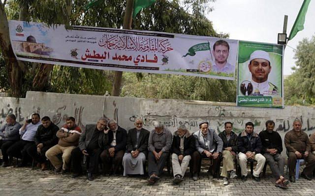 Los palestinos se reúnen de luto frente a la casa familiar del profesor de 35 años y miembro de Hamas Fadi Mohammad al-Batsh, quien murió temprano en Malasia, en Jabalia, en la franja norte de Gaza, el 21 de abril de 2018. (AFP PHOTO / MAHMUD HAMS)