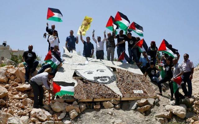 Activistas palestinos se paran alrededor de un retrato en mosaico de 5 × 4 metros (16.5 × 13 pies) de Marwan Barghouti cerca de una instalación militar israelí en la ciudad de Ramallah, martes, 9 de mayo de 2017. (AP Photo / Nasser Shiyoukhi)