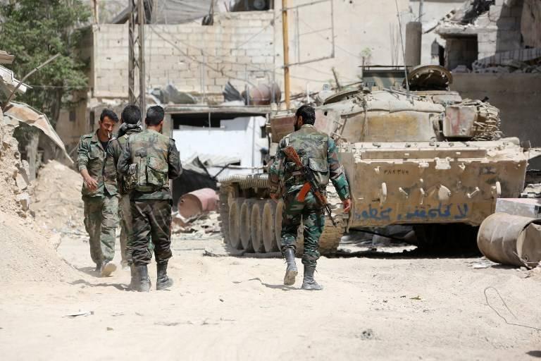 Una fotografía tomada el 8 de abril de 2018 muestra a los soldados del ejército sirio reunidos en un área en las afueras del este de Duma, mientras continúan su ofensiva para retomar el último enfrentamiento en Ghouta Oriental.(AFP Photo / Stringer)