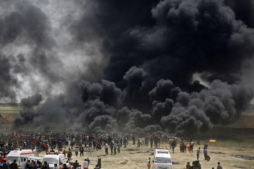 Los islamistas palestinos queman neumáticos en la valla fronteriza con Israel, al este de Jabalia, en la ciudad central de Gaza, el 13 de abril de 2018. (AFP PHOTO / MOHAMMED ABED)