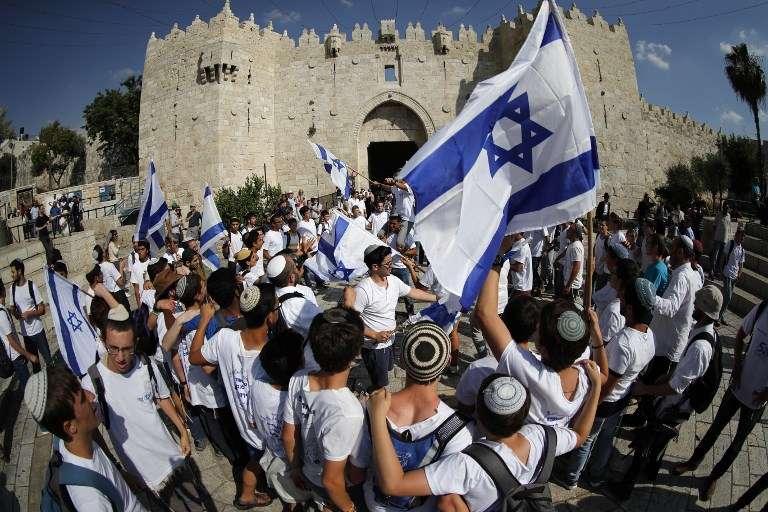 Los israelíes agitan banderas mientras celebran el Día de Jerusalem a las afueras de la Puerta de Damasco en la Ciudad Vieja de Jerusalem el 24 de mayo de 2017. (AFP PHOTO / Thomas COEX)