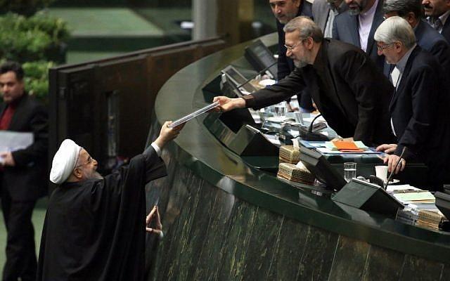 El presidente iraní, Hassan Rouhani, izquierda, presenta el presupuesto anual propuesto al presidente del Parlamento, Ali Larijani Ali Larijani, en la capital, Teherán, el 17 de enero de 2016, luego de que se levantaran las sanciones bajo el acuerdo nuclear de Teherán con las potencias mundiales.(AFP / Atta Kenare)